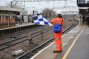 Railway worker wearing high visibility orange clothing holds blue and white checkered safety flag, Colchester, Essex, England, UK