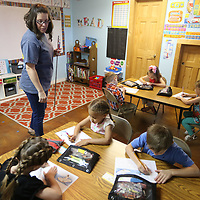 Alexis Willardson, the K-4 and 5 teacher at Creo Christian School in Nettleton, watches over her class as they work on their cursive writing excerise during class on Tuesday morning. The school offers an alternative to both public school and other more traditional Christian private schools.