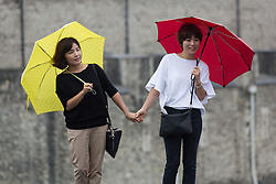 © Licensed to London News Pictures. 19/08/2016. LONDON, UK.  Tourists with umbrellas near the River Thames path during a rain shower. Following the UK's mini heatwave this week, weather forecasters have issued a severe weather warning, predicting a spell of wet and stormy weather across the country..  Photo credit: Vickie Flores/LNP