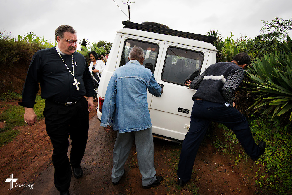 LCMS President Matthew C. Harrison surveys a vehicle stuck in the mud on the road to a Lutheran church near Antsirabe, Madagascar, on Wednesday, Feb. 5, 2014. LCMS Communications/Erik M. Lunsford