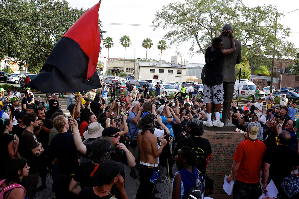 A protestor ties a bandana to a statue after a march through the streets during the 2012 Republican National Convention in Tampa, Fla. on Aug. 28, 2012. Photo by Greg Kahn