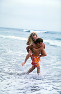 Lifestyle image of young couple playing on the beach in Carlsbad, CA.