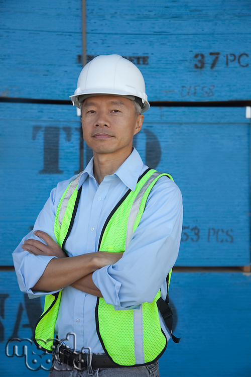 Portrait of a middle-aged warehouse worker standing with arms crossed