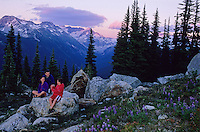 Family relaxes on a boulder during an evening hike on Whistler Mountain, BC, Canada.