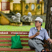 Elderly man sitting on park bench at Tao Dan Park, Saigon