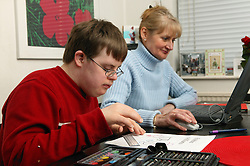 Single parent working on a computer while her son does his homework,