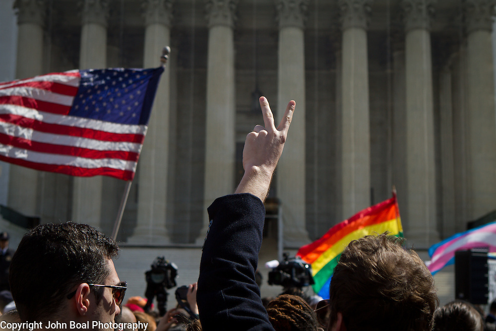 A peace sign flashes in the air during demonstrations outside the Supreme Court during the hearings about the constitutionality of Defense of Marriage Act (DOMA). March 27, 2013. John Boal Photography.