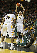 February 2 2011: Iowa Hawkeyes forward Jarryd Cole (50) puts up a shot over Michigan State Spartans forward Draymond Green (23) during the first half of an NCAA college basketball game at Carver-Hawkeye Arena in Iowa City, Iowa on February 2, 2011. Iowa defeated Michigan State 72-52.