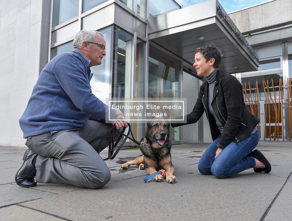 Pictured: Finn with owner PC Dave Wardell and Minister for Rural Affairs Mairi Gougeon at the Scottish Parliament.<br /> <br /> Former police dog Finn, whose campaign to protect service animals has seen the introduction of 'Finn's Law' in England and Wales, went to the Scottish Parliament, who have announced plans to introduce similar legislation in Scotland.<br /> <br /> © Dave Johnston / EEm