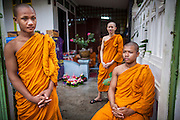28 NOVEMBER 2012 - BANGKOK, THAILAND:  Buddhist monks wait for people to arrive to celebrate Loy Krathong at Wat Yannawa in Bangkok. Loy Krathong takes place on the evening of the full moon of the 12th month in the traditional Thai lunar calendar. In the western calendar this usually falls in November. Loy means 'to float', while krathong refers to the usually lotus-shaped container which floats on the water. Traditional krathongs are made of the layers of the trunk of a banana tree or a spider lily plant. Now, many people use krathongs of baked bread which disintegrate in the water and feed the fish. A krathong is decorated with elaborately folded banana leaves, incense sticks, and a candle. A small coin is sometimes included as an offering to the river spirits. On the night of the full moon, Thais launch their krathong on a river, canal or a pond, making a wish as they do so.   PHOTO BY JACK KURTZ