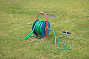 rolled up garden water hose on grass