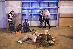 © Licensed to London News Pictures . Manchester , UK . 05/04/2015 . Two men lie on the pavement on Withy Grove in Manchester City Centre as a beat-boxing duo perform . Revellers on a Saturday night out during the Easter Bank Holiday weekend . Photo credit : Joel Goodman/LNP