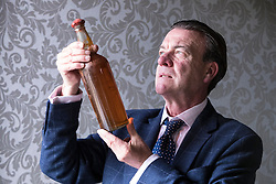 Bonhams whisky sale in Edinburgh on 7 June includes two salvaged bottles from the wreck of the SS Politician which were the inspiration for Compton MacKenzie's novel Whisky Galore. Also included in the sale is a 50 year-old Macallan Millennium Decanter distilled in January 1949.<br /> <br /> Pictured: Bonham's Whisky Consultant, Martin Green with Gilbey's - circa 1940 estimate £6,000 - £8,000.