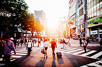 Crowds walk through the Shinjuku neighborhood of Tokyo, Japan, as the late afternoon sun sets in the distance.