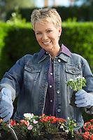 Senior woman planting flowers, portrait