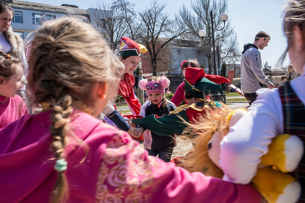 Children play a game with women dressed as clowns in a public park on Orthodox Easter on Sunday, April 12, 2015 in Donetsk, Ukraine.