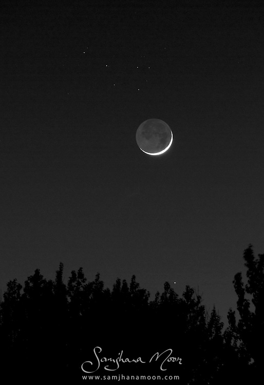 The new Moon, Mercury and the Pleiades star cluster gathered close on the horizon in a three-way conjunction. The dark lunar terrain is visible to stargazers due to reflected sunlight from the Earth surface, what is commonly known as Earthshine.