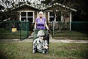 Suzie Champoux holds the picture of her daughter, Sgt. Sophie Champoux, in front of her house in Florida.