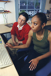 Single mother and teenage daughter using computer,