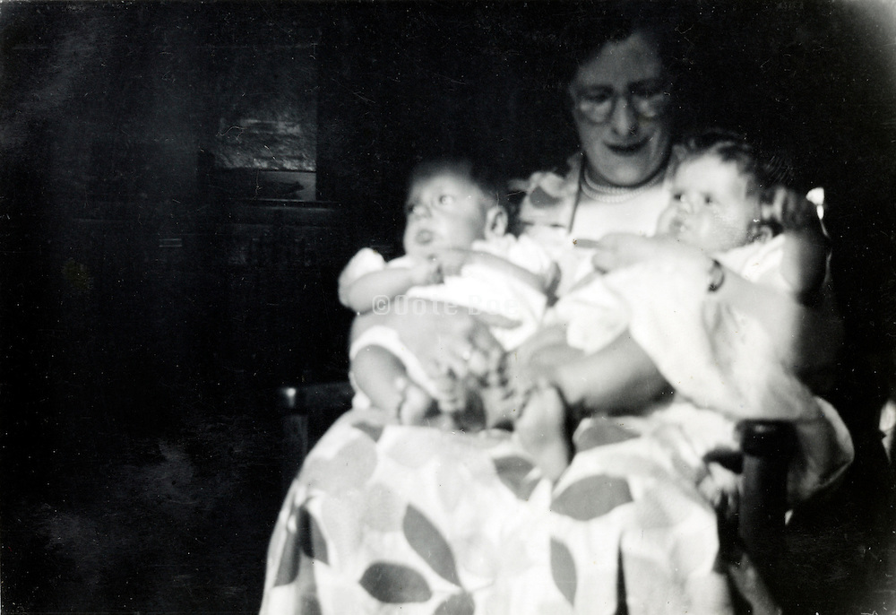 mother holding twin babies 1950s