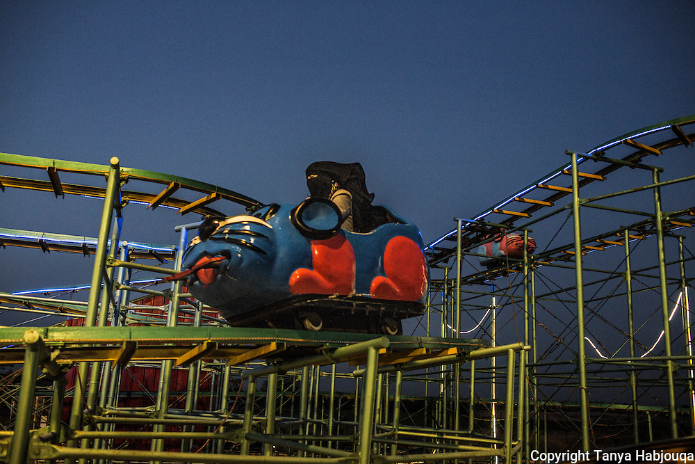 A woman enjoys a quiet ride on a children's coaster at Sharm Park City in Gaza.