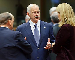 George Papandreou, Greece's prime minister, center, speaks with Silvio Berlusconi, Italy's prime minister, left, and Helle Thorning-Schmidt, Denmark's prime minister, right, during an emergency EU Summit to solve Europe's debt crisis at the European Council headquarters in Brussels, Belgium, on Wednesday, Oct. 26, 2011. (Photo © Jock Fistick)