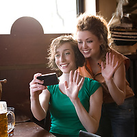 two friends waving at the smartphone, indoor setting