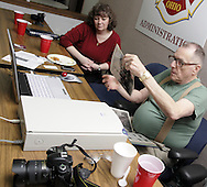 Lori Naughton, from Fairborn watches as Alan Routt scans photos at a reunion of Fairborn fire fighters at the Fire Administration offices, Friday, April 11, 2008.