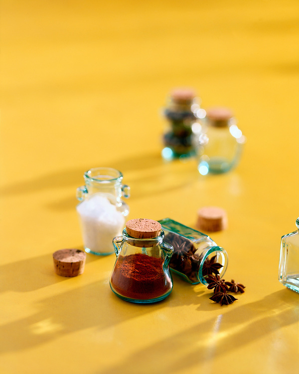 A small selection of spice bottles with corks sit on an ochre background