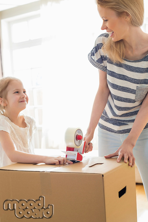 Mother and daughter looking at each other while packing cardboard box at home