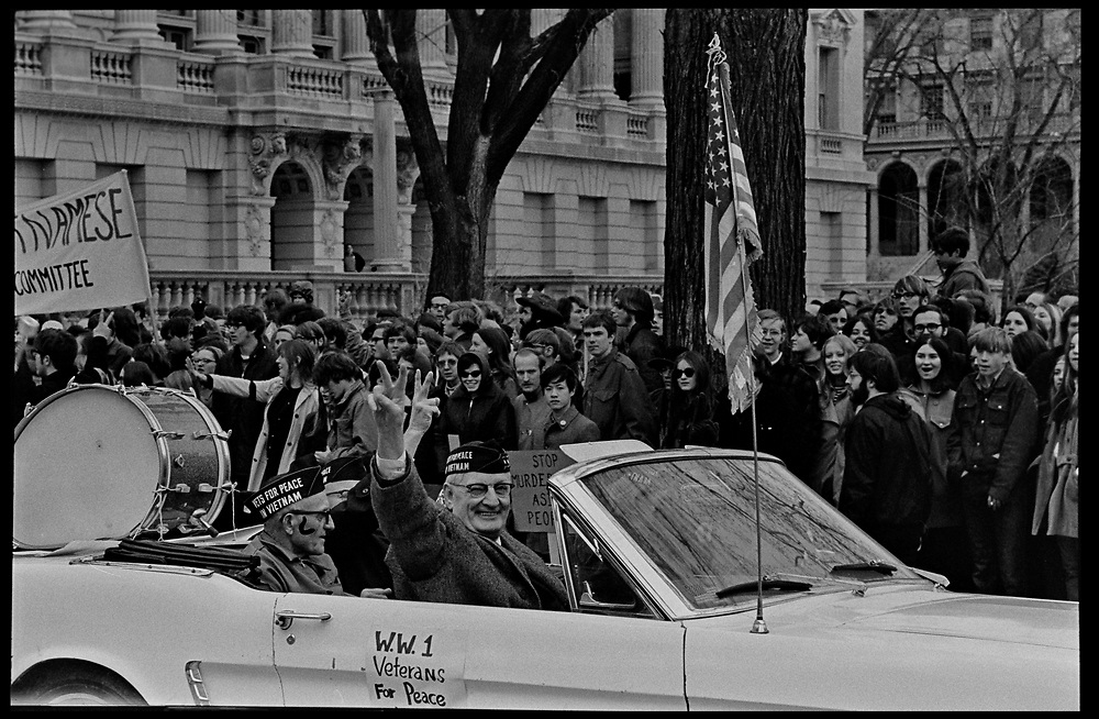 Madison, WI – May, 1970. Protesters against the war in Vietnam march up State Street towards the Capitol, led by Veterans for Peace in Vietnam. On May 1, 1970, there was a general student strike in response to the news that the U.S. had expanded bombing into Cambodia. There was a march against the war, led by Veterans for Peace in Vietnam; and after the May 4 shootings at Kent State University in Ohio, there were more protests at UW Madison, which led to the police being called in, and teargassing demonstrators in the streets and on campus. The car carries W.W.I Veterans for Peace.