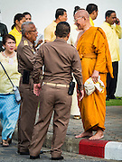 09 JUNE 2016 - BANGKOK, THAILAND: A Buddhist monk talks to workers from the Grand Palace before a special merit making ceremony Thursday. Thailand marked 70 years of the reign of Bhumibol Adulyadej, the King of Thailand, with a special alms giving ceremony for 770 monks in front of the Grand Palace in Bangkok. The King, also known as Rama IX, ascended the throne on 9 June 1946. He is the longest serving monarch in Thai history and the longest serving monarch in the world today. He is revered by most Thais and is widely seen as a unifying figure in the country.     PHOTO BY JACK KURTZ