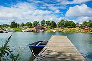 Roddbåt vid brygga vid stugor på Rödlöga i Stockholms skärgård