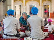 "08 FEBRUARY 2015  BANGKOK, THAILAND: A woman makes an offering in the Darbar Sahib (prayer hall) at Gurdwara Siri Guru Singh Sabha, the Sikh temple in Bangkok. Thailand has a small but influential Sikh community. Sikhs started coming to Thailand, then Siam, in the 1890s. There are now several thousand Thai-Indian Sikh families. Gurdwara Siri Guru Singh Sabha was established in 1913. Construction of the current building, adjacent to the original Gurdwara (""Gateway to the Guru""), started in 1979 and was finished in 1981. The Sikh community serves a daily free vegetarian meal at the Gurdwara that is available to people of any faith and background.    PHOTO BY JACK KURTZ"