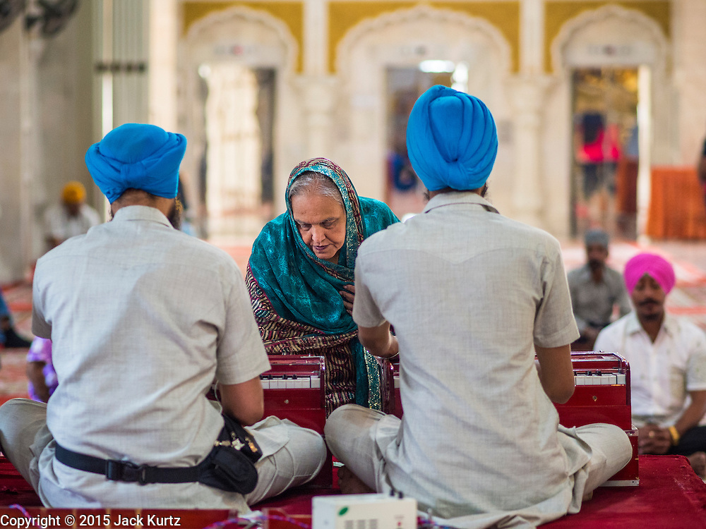 """08 FEBRUARY 2015  BANGKOK, THAILAND: A woman makes an offering in the Darbar Sahib (prayer hall) at Gurdwara Siri Guru Singh Sabha, the Sikh temple in Bangkok. Thailand has a small but influential Sikh community. Sikhs started coming to Thailand, then Siam, in the 1890s. There are now several thousand Thai-Indian Sikh families. Gurdwara Siri Guru Singh Sabha was established in 1913. Construction of the current building, adjacent to the original Gurdwara (""""Gateway to the Guru""""), started in 1979 and was finished in 1981. The Sikh community serves a daily free vegetarian meal at the Gurdwara that is available to people of any faith and background.    PHOTO BY JACK KURTZ"""