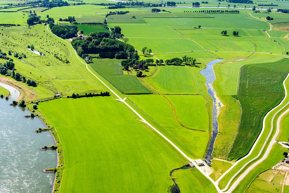 Nederland, Gelderland, Gemeente Brummen, 17-07-2017; rivier de IJssel, dijkverlegging Cortenoever. Cortenoever met Brummense Bandijk, gezien naar het zuidoosten. Plangebied voor dijkverlegging. Er is een nieuwe dijk aangelegd,  rechts parallel het landweggetje.  De oude dijk (midden, naar boven) is verlaagd en heeft een uitstroomopening ongeveer tussen het nieuwe gemaal en tot aan de bosschages. Het gebied tussen oude en nieuwe dijk is meestroom-gebied in geval van hoog water. NOOT: Zie ook opnames van de oorspronkelijke situatie.<br /> Shifting the Cortenoever dike. A new (secondary) dike has been build, to the right and in line with the road)). The existing dike (below - to the woods) has been reduced in height to the to create exit opening. The area between old and new dike will flood in case of high water.<br /> See also recordings of the original situation.<br /> luchtfoto (toeslag op standard tarieven);<br /> aerial photo (additional fee required);<br /> copyright foto/photo Siebe Swart