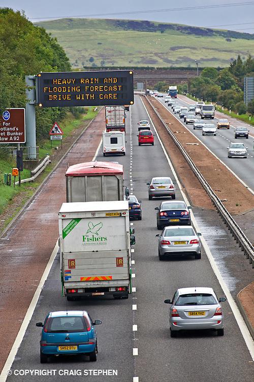Busy motorway with gantry warning sign - M90 in Fife, Scotland near Forth road bridge.