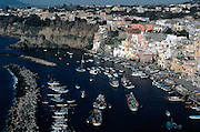 Italy. Procida Island in the Bay of Naples. Brightly painted fishermen's cottages and and the harbour at Corricella.