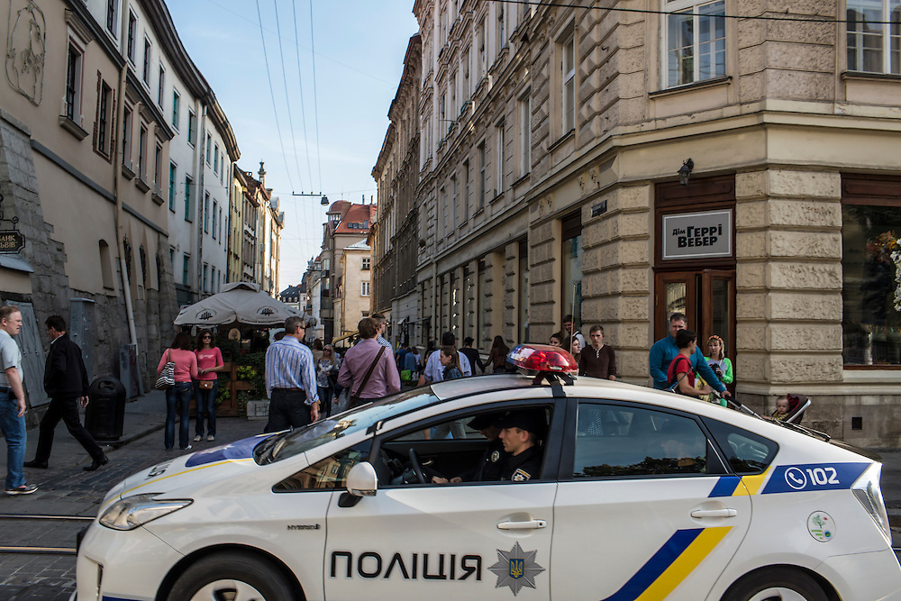 LVIV, UKRAINE - SEPTEMBER 15, 2015: Members of the new police patrol Market Square, the tourist-friendly central square, in a new Toyota Prius donated by the government of Japan in Lviv, Ukraine. In an effort to reform the notoriously corrupt Ukrainian police force, an entirely new force has been established in several cities, including Kiev and Lviv, with a primary focus on patrolling the streets. CREDIT: Brendan Hoffman for The New York Times