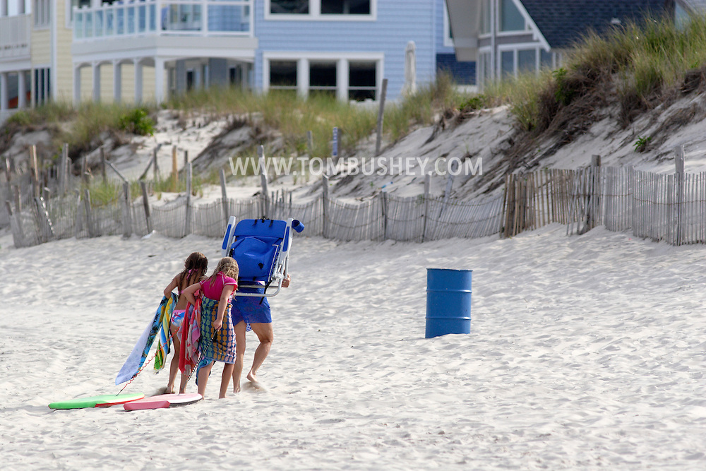 Beach Haven, NJ - A man carries a chair and two young girls drag their boogie boards across the sand as the leave the beach for the day at Long Beach Island on July 13, 2007.