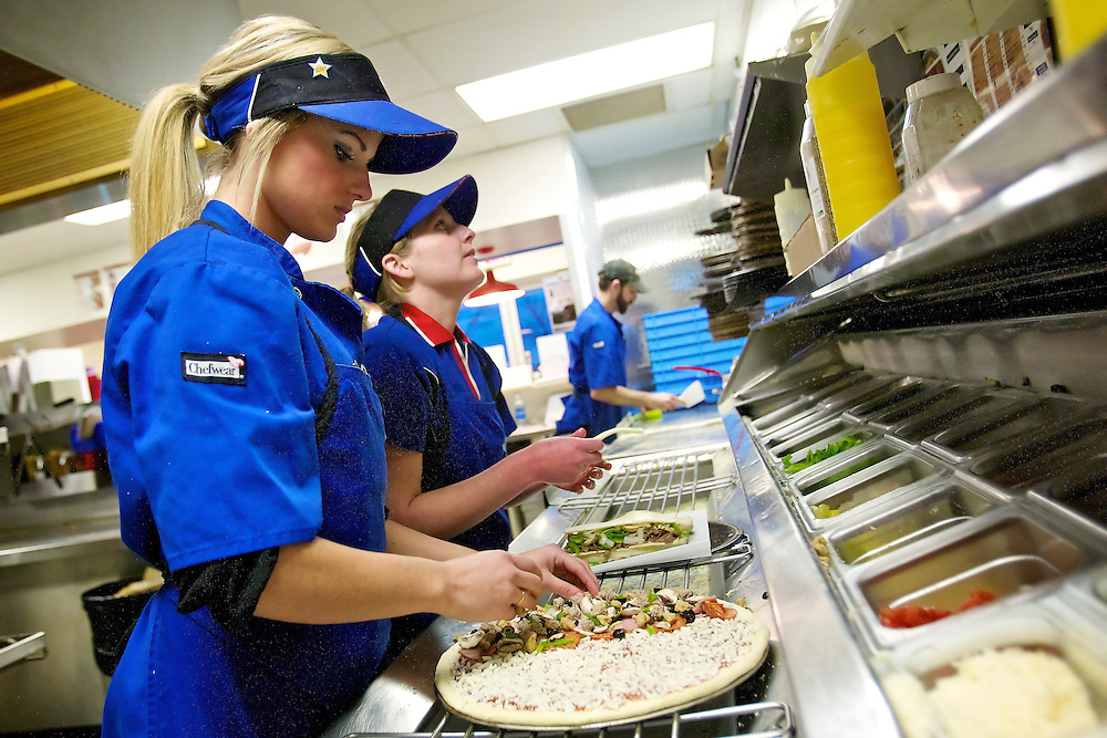 Carlie Paquin, left, general manager of the Domino's in Coeur d'Alene, and Jennifer Crain prepare pizzas orders Thursday during the dinner rush. The four Domino's Pizza stores in the area plan on preparing 1,500 pizzas on Sunday for customers hosting Super Bowl parties.