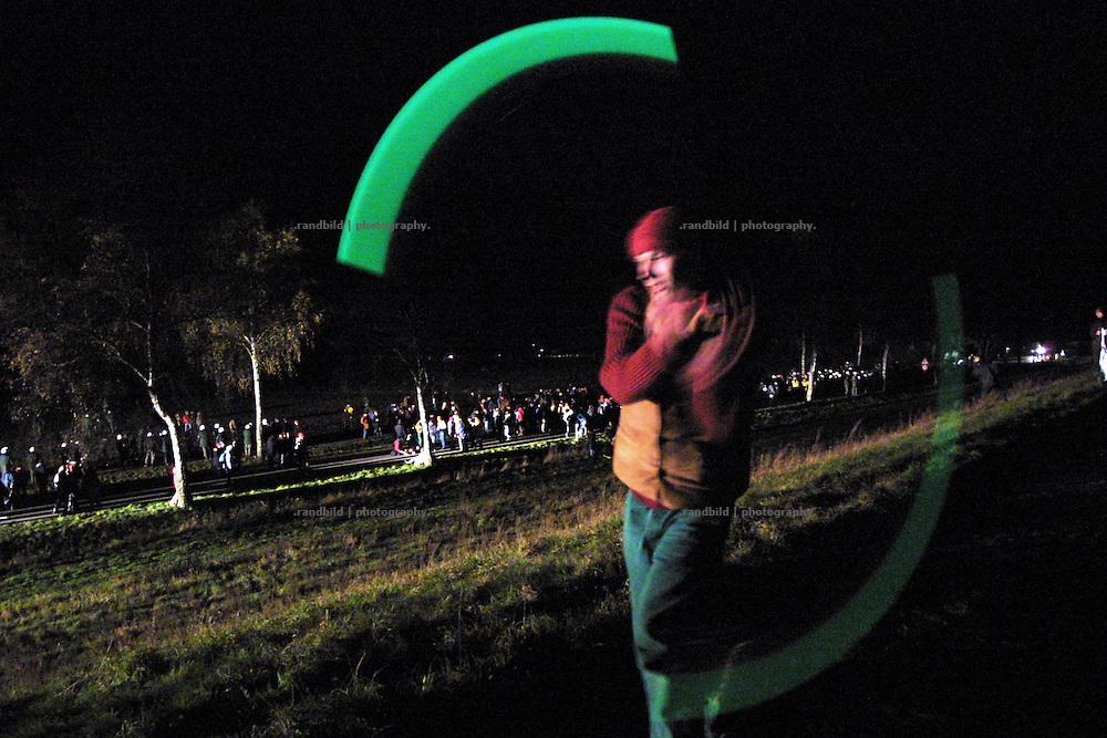 Am Rande eine Sitzblockade (hinten) bei Gorleben jongliert ein Künstler auf dem Elbedeich mit zwei Lichterketten. Die Blockade richtete sich gegen einen Atomtransport mit 12 Castorbehältern ins Zwischenlager Gorleben.