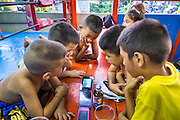 "18 DECEMBER 2104 - BANGKOK, THAILAND: Boys who want to become boxers drink energy drinks and watch videos on a smart phone at the Kanisorn gym. The Kanisorn boxing gym is a small gym along the Wong Wian Yai - Samut Sakhon train tracks. Young people from the nearby communities come to the gym to learn Thai boxing. Muay Thai (Muai Thai) is a Thai fighting sport that uses stand-up striking along with various clinching techniques. It is sometimes known as ""the art of eight limbs"" because it is characterized by the combined use of fists, elbows, knees, shins, being associated with a good physical preparation that makes a full-contact fighter very efficient. Muay Thai became widespread internationally in the twentieth century, when practitioners defeated notable practitioners of other martial arts. A professional league is governed by the World Muay Thai Council. Muay Thai is frequently seen as a way out of poverty for young Thais and Muay Thai camps and schools are frequently crowded. Muay Thai professionals and champions are often celebrities in Thailand.     PHOTO BY JACK KURTZ"