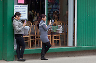 Middletown, New York - Two women stand outside a restaurant with their cell phones to watch Members of St. Joseph's Church march through the city during the festival of Nuestra Senora de Guadalupe on Sunday, Dec. 9, 2012.