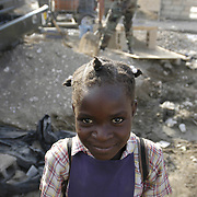 "Melda Alchideau, 6, of Gonaives, Haiti attends Ecole N. D. de la Nativite, in Gonaives, Haiti.  Behind her are U.S. Navy Seabees constructing a new school building for her and her classmates.  After the hurricanes of 2004, flood waters were more than 12 feet deep at this location.  When asked what she thought of the work being done, she said, ""Tres bien,"" which translates to ""very good.""  <br />