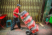 "06 MARCH 2013 - BANGKOK, THAILAND:  A soft drink delivery man on his rounds in Bangkok. Thailand's economic expansion since the 1970 has dramatically reduced both the amount of poverty and the severity of poverty in Thailand. At the same time, the gap between the very rich in Thailand and the very poor has grown so that income disparity is greater now than it was in 1970. Thailand scores .42 on the ""Ginni Index"" which measures income disparity on a scale of 0 (perfect income equality) to 1 (absolute inequality in which one person owns everything). Sweden has the best Ginni score (.23), Thailand's score is slightly better than the US score of .45.  PHOTO BY JACK KURTZ"