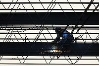 An ironworker welding the steel framework of a building.