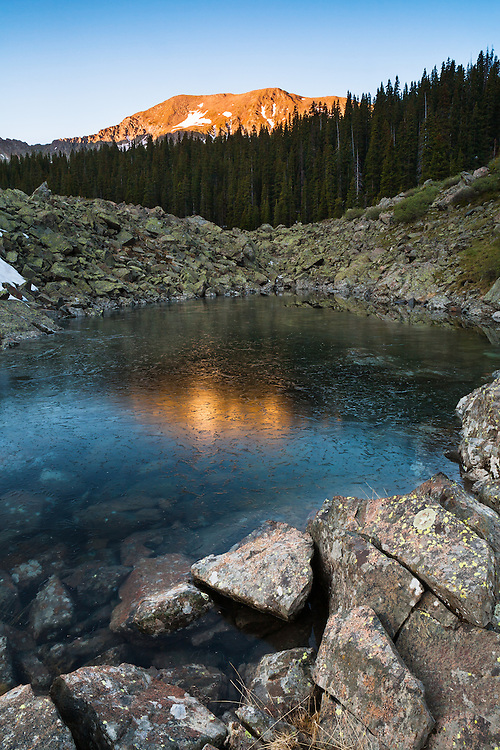 An unnamed mountain reflects in small frozen pond. Wheeler Peak Wilderness near Taos, New Mexico.
