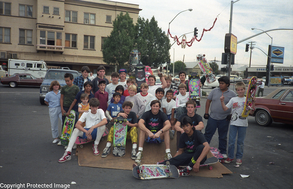 A team of skateboarders including Tom Knox and Karma Tsocheff pose with local kids during a skateboarding demo at Skateboard Mania skateboard shop during 1986 in Porterville, California.