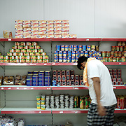 August 09, 2013 - Zarqa, Jordan: A syrian refugee picks up groceries at the well stocked supermarket of Mrigb Al-Fuhud refugee camp, also known as Emirates-Jordanian camp, 20 kilometres east of the Jordanian city of Zarqa. The refugees at the camp are given weekly vouchers with which they can purchase goods.<br /> The 10 million USD camp, which has 750 caravans, a hospital, and a school and can take up to four thousand people, first opened in April 2013 and was paid for by the United Arab Emirates. Work is underway to house a total of 20 thousand by the end of the year.<br /> In contrast with the two other camps in the area, Mrigb Al-Fuhud as been classified by many as a 'five star' camp due to impressive housing facilities provided to the refugees. (Paulo Nunes dos Santos/Al Jazeera)